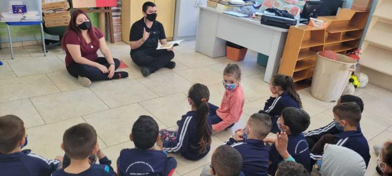 Associados fazendo leitura para as crianças da escola na atual biblioteca (antes da reforma).